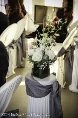 Centerpiece arrangement tops columns with gray sash for indoor winter wedding