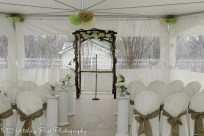 Columns topped with flowers used down the aisle under the tent