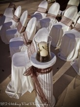 Coffee and candle centerpiece tops column as aisle decor
