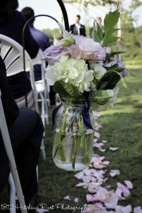 Pink and lilac roses with white hydrangeas in mason jar tied with navy ribbon