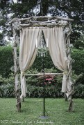 Rustic arbor with burlap curtains and chandelier