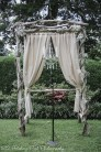 Rustic arbor with live babies breath, burlap curtains and chandelier