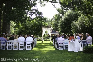 Ceremony under oaks with rented chairs