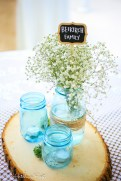 Trio of blue mason jars with candles and babies breath