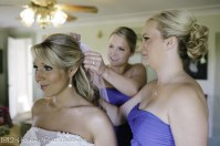 Bridesmaids adjust bride's hair