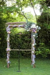 Silk eucalyptus, lilac and Tangerine silk peonies with bride provided tulle. Rustic wood cross.