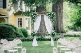 Live white flowers and greenery at corners and tiebacks. White drapes