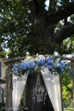 White curtains, chandelier, blue silk flowers