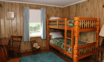 Log cabin quilts on bunks; extra cot under bunks