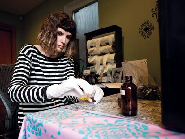 Siems pours sample sizes of perfume in her studio.