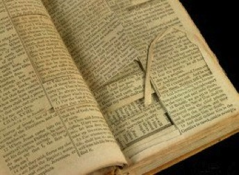 Jefferson Bible Source books open to cut-up pages to show the missing pieces