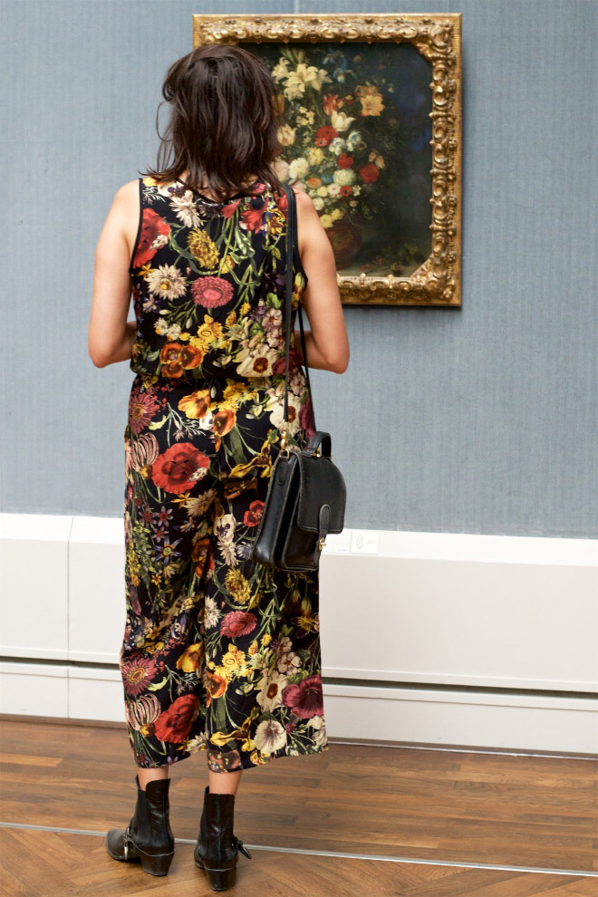 Woman's dress perfectly matching a painting in an art museum.