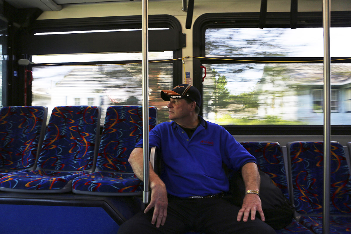A man in a baseball hat and blue shirt rides a city bus alone, with trees and houses rushing by the windows