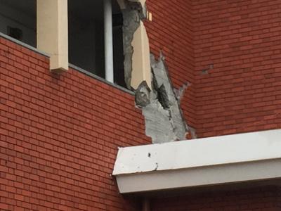 外壁が剥がれ落ち鉄筋が見えているマンション
