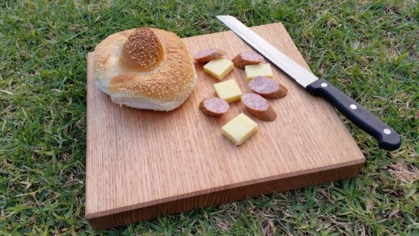 close up of small chopping board with cheese knife and cabana