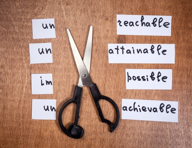 Une paire de ciseaux découpe la premiere syllabe de inaccessible, inatteingnable, impossible, irréalisable.