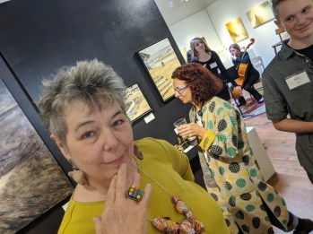 Showing off the jewelry I am modeling during the opening