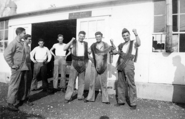 Gunners load up with heavy belts of linked .50 caliber ammo at the property shed. From left: three unknown Marines, Jim Pritchett, Charles Podolski, Charles Czerweic, Carmen Ramputi. New River, 1942.