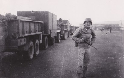 """An officer poses at the head of another convoy. The vehicles appear to be the 2.5 ton """"6x6"""" trucks made by International Harvester."""