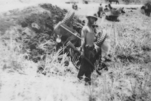 Back in the thick of things. A shirtless and grimy John Pope on Saipan, with a capsized Japanese truck.