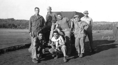 Corpsmen pose around an ambulance jeep. Haynes, Hearn, Middlewood, and Flores are present.