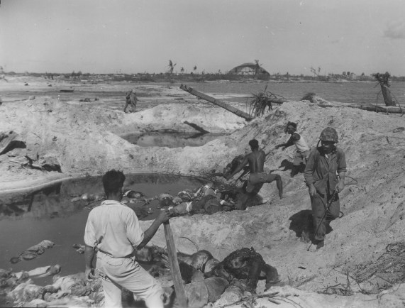 """Natives help US Marines move dead Jap bodies on island."""