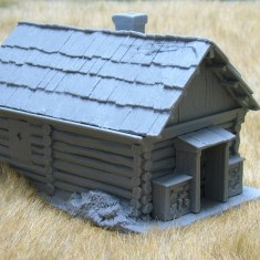 Large cabin with shingle roof and porch.