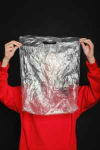 person wearing red top holding clear plastic bag