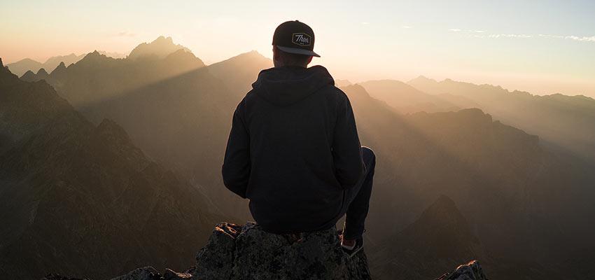 Man sitting in a mountain range.