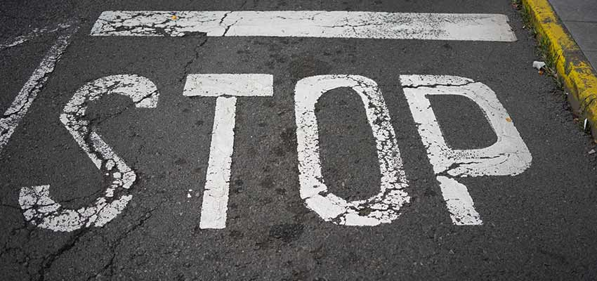 """A road with """"STOP"""" painted on it."""