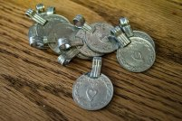 Multiple plain kuchi coins with bail attachments for using as a pendant