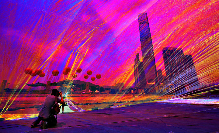 """Apartment towers and the International Commerce Centre, tower at center, are seen through a work of art entitled """"Poetic Cosmos of the Breath"""" by Argentine artist Tomas Saraceno, which is part of an exhibition called """"Mobile M+: Inflation!"""" at the waterfront of West Kowloon Cultural District in Hong Kong Wednesday, April 24, 2013. (AP Photo/Vincent Yu)"""