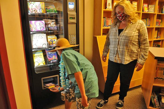 Unsworth elementary school librarian, Lorraine Warner, watches as Grade 5 student, Zachary Greenwood, retrieves his new book from the school's book vending machine on Friday, Oct. 16, 2020. (Jenna Hauck/ Chilliwack Progress)