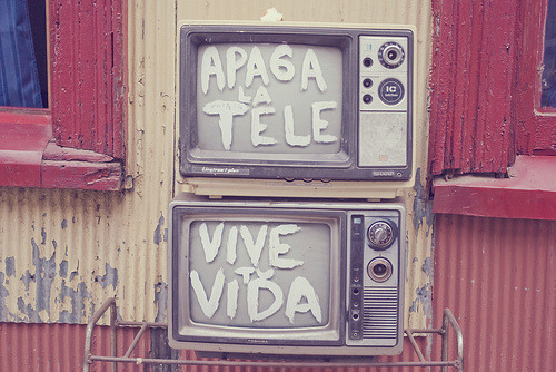 """I was walking in Valparaíso, Chile, and two TV's where just outside a house.  It says """"Turn off the TV - Live your life"""""""