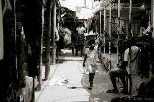 A girl carries some goods through the market.