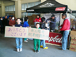 """Two boys hold up a sign made from a cardboard box that reads, """"Thank you, from all of us at the Utatsu Evacuation Center."""""""