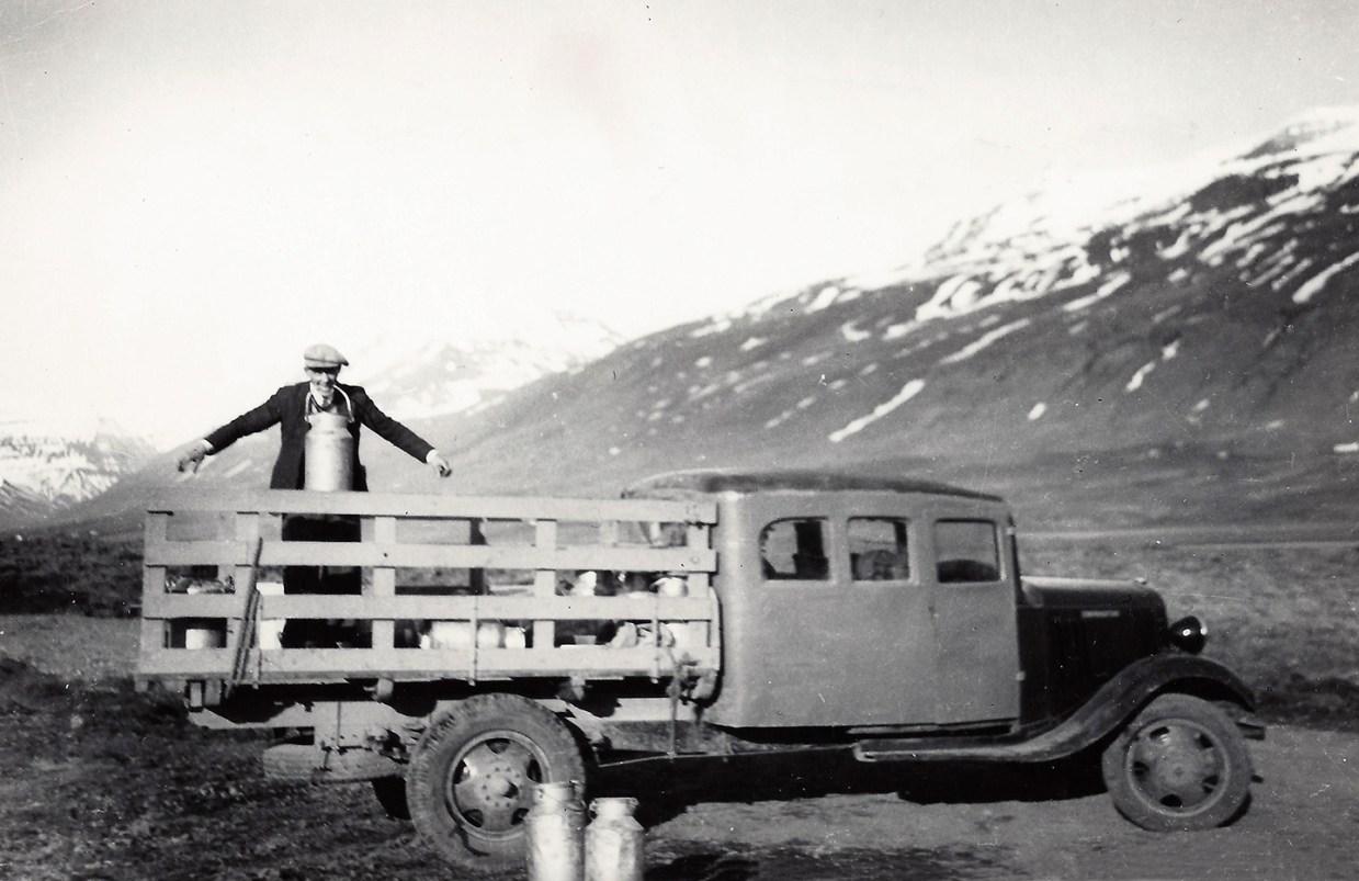 Gestur Hjörleifsson (1908) fyrsti mjólkurbílstjórinn 1934 – 1936. Þessi fyrsti bíll tók 5 farþega og var aðeins notaður við sumarakstur. Takið eftir aflrauninni sem Gestur er að sýna. Myndin er líklegast tekin við Sandá í Svarfaðardal 1935 eða 1936. (Úr safni Jónasar Hallgrímssonar)