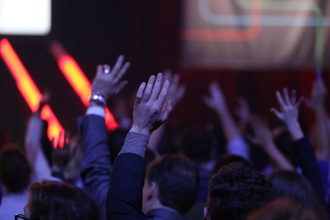 Le public lève les mains pendant une conférence