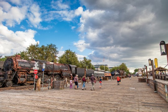 Family walking past a steam locomotive on the Old Sacramento Riverfront.