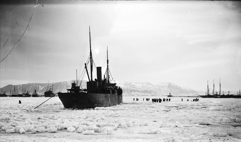 Hópur manna úti á ísnum við Reykjavíkurhöfn 1918. Esjan í baksýn.