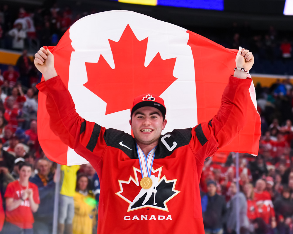 ba8bc611 Canada's captain Dillon Dube #9 waves the flag following his team's victory  against Sweden during the gold medal game of the 2018 IIHF World Junior ...