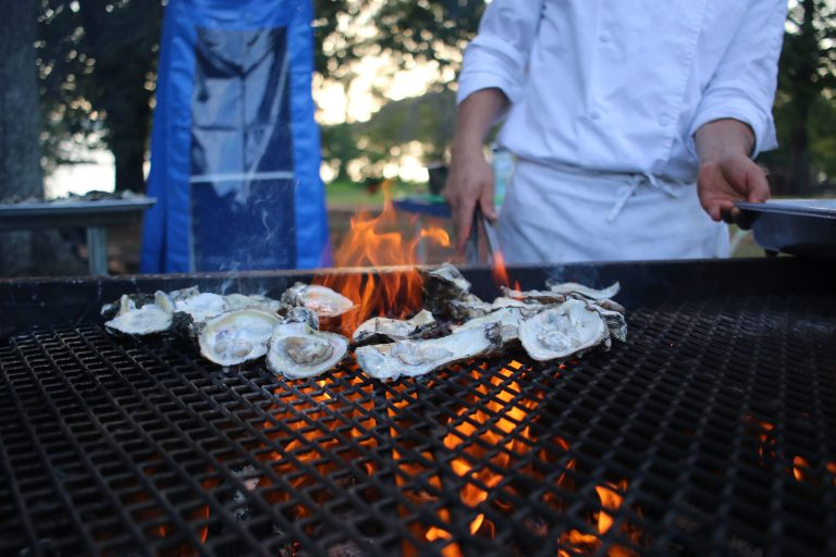 A photo of oysters being grilled