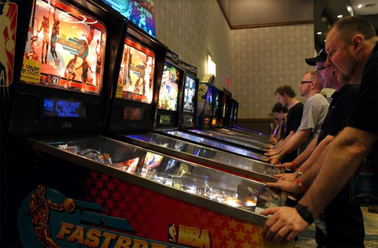 A photo of people playing pinball