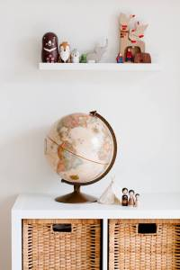 retro toys and globe on cabinet in nursery room