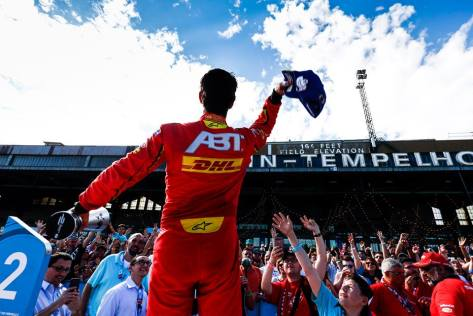 Formula E driver in red jumpsuit facing a crowd eager for his cap which he wants to toss into the crowd