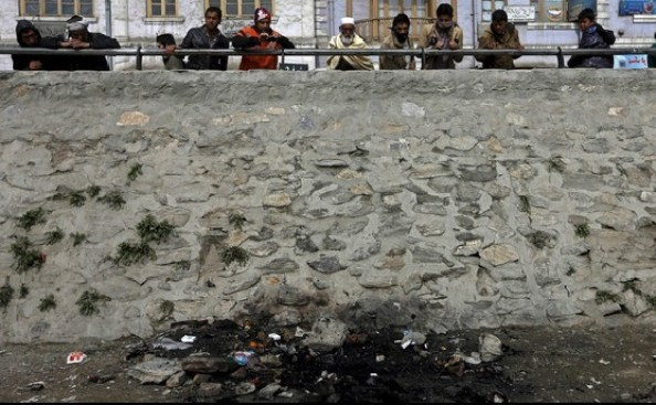 Afghan men look at the site where an Afghan woman was beaten to death and her body set on fire in Kabul