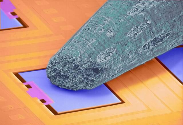 Barevný snímek pořízený elektronickým mikroskopem přibližuje plochu mikroskopického měřiče zrychlení z automobilového airbagu.
