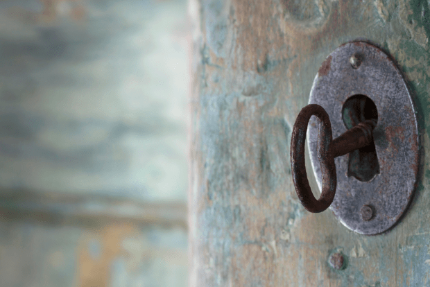 photo shows a rusty key in a rusty keyhole on a wooden door