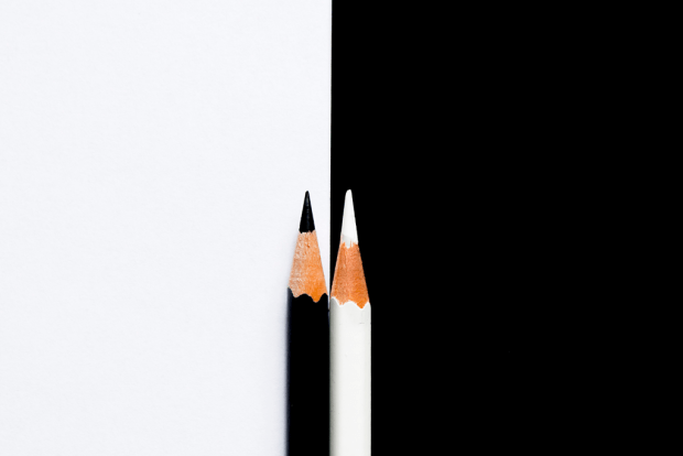 photo shows a black pencil on a white background next to a white pencil on a black background