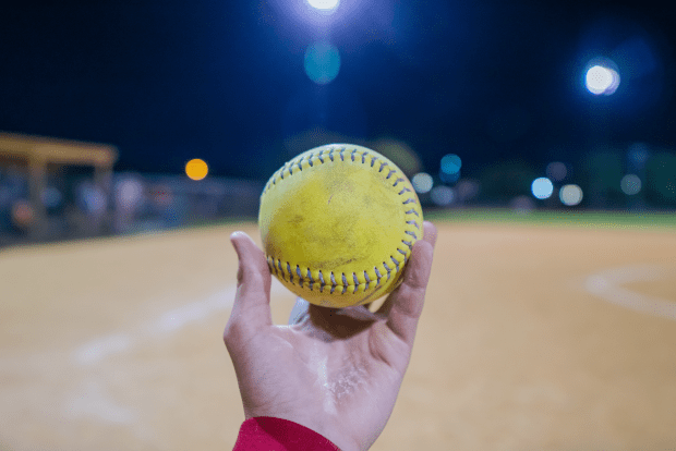 photo shows a hand holding a softball in front of a lit field
